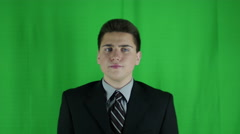 Young businessman sits waiting in front of greenscreen Stock Footage