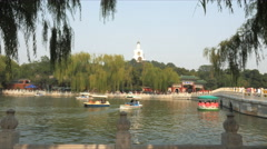 Paddle boats on a lake and the white dagoba in beijing's beihai park Stock Footage