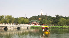 Yellow boat on a lake and the white dagoba of beihai park Stock Footage