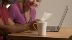 Middle aged baby boomer models using technology to pay bills online Stock Footage