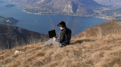 Working with the computer in front of a beautiful landscape Stock Footage