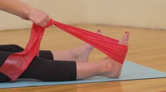 Close up of womans feet streching using exercise band Stock Footage