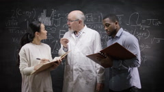 4K Academic group in front of blackboard with math formula discussing ideas - stock footage