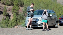 Mother and girl stand near car which is parking small lay-by space, Tenerife Stock Footage