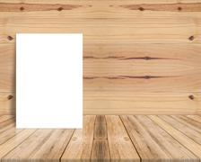 Blank poster leaning at plank wood wall and diagonal wooden floor. Stock Photos