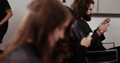 A young model at a hair salon having her done while taking a photo on her phone Stock Footage