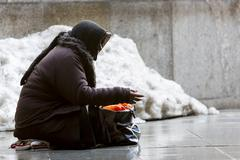 Anonymous female beggar - stock photo