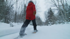 Low Angle of Young Woman Walking with Snowshoes in Forest Stock Footage