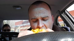 A man eating fast food in his car Stock Footage