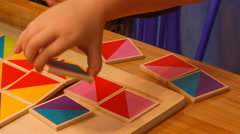 Stock Video Footage of closeup child's hands compose wooden puzzle on table