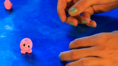Mother's hands sculps toy of blue plasticine near pink toy pig Stock Footage