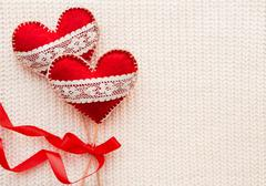 White woven background with two felt hearts with laces, symbol of love. Good - stock photo