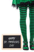 black and green striped legs from a leprechaun girl, slate with text happy st - stock photo