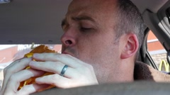 Man eating fast food in his car Stock Footage