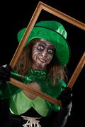 madly leprechaun behind a wooden frame, black background - stock photo