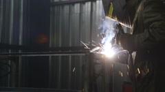 Welder welding metal material in heavy industry Stock Footage