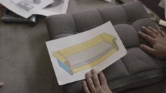 Two men look at drawing sofa and discuss it in furniture factory Stock Footage