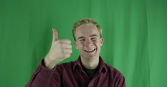 Handsome young man gives thumbs up to camera on greenscreen Stock Footage