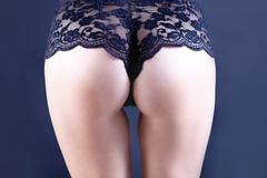 Closeup of a sexy woman's back wearing black lingerie isolated - stock photo