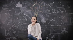 4K Portrait of thinking woman sitting in front of blackboard with math formulas - stock footage