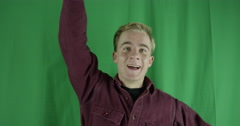 Handsome young man waves to an old friend on a greenscreen Stock Footage