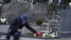 Father man put candle on daughter son grave in graveyard. 4K - stock footage