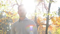 Handsome young satisfied guy stands in the forest and looks to camera- sun rays Arkistovideo