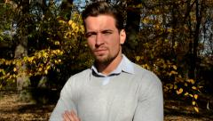 View on a young handsome serious man who stands in the woods and looks to camera Stock Footage