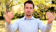 Young handsome man stands in the woods, stare to camera and with his hands shows Stock Footage