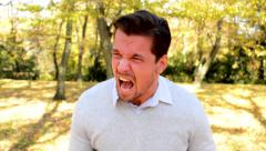 A handsome young man stands in the woods, is angry Stock Footage