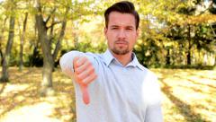 Young man stands in the woods and with serious face shows thumb down Stock Footage