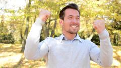 Young man stands in the woods, has a great joy and is happy Stock Footage