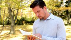Young man stands in the woods and with interest reads a book Stock Footage