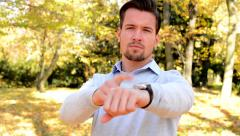 Young man stands in the woods and with a serious face shows on watch Stock Footage