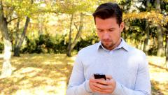 Young man stands in the woods, thinks about something and works  on the phone Stock Footage