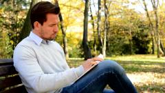 Young man sits on bench in a park and with interest reads a book Stock Footage