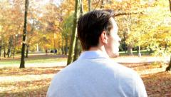 A young man goes through the woods, is turned back and looks around  Stock Footage