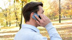 View of a young man turns back, who goes through the woods and phone Stock Footage