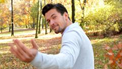 Young handsome man walks through the forest and shows to someone to follow him Stock Footage