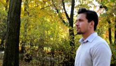 Overall detailed view of a young handsome man who is walks through the woods Stock Footage