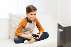 Happy boy with joystick playing video game at home Kuvituskuvat