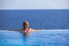 woman relaxing in infinity pool in summer - stock photo