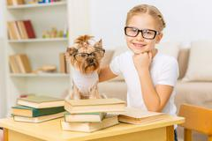 Little girl and her dog wearing glasses - stock photo