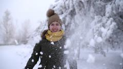 Woman throwing a snowball into the camera - stock footage
