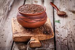 flax seeds in bowl on a wooden table - stock photo