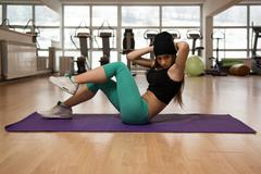 Beautiful Young Women Working Out Abs On Mat - stock photo