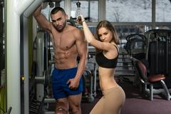 Young Couple Doing Exercise For Triceps On Machine Stock Photos
