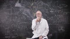 4K Portrait of thinking man sitting in front of blackboard with math formulas Stock Footage