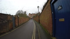 4K POV walking along bricked lane with blue door and double yellow lines Stock Footage