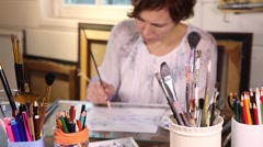 Middle age woman painting with watercolors in art studio with brushes in foregro - stock footage